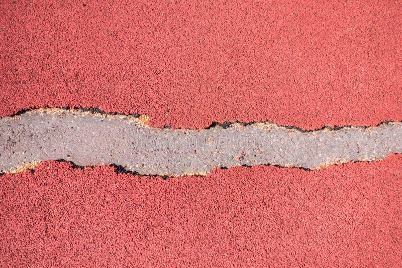 Vieille couverture en caoutchouc rouge d?chir?e de miette, tapis roulant ou fond ext?rieur ext?rieur de texture de stade de terra images libres de droits