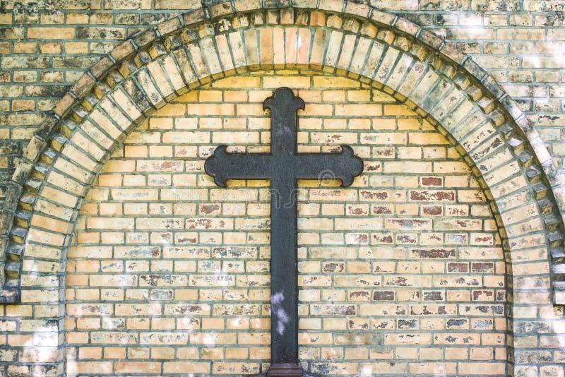 Vieille croix en métal sur le fond de mur de briques, croix rouillée sur la tombe photographie stock