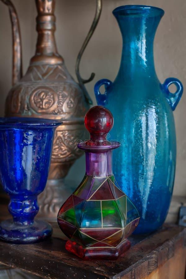 Vieille cruche orientale et bouteilles bleues photos stock