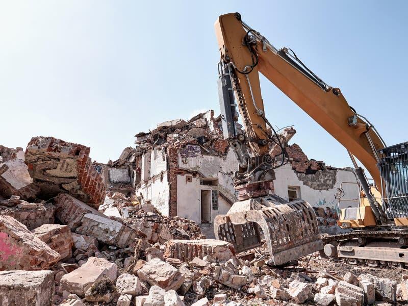 Vieille démolition de maison Fonctionnement d'excavatrice en blocaille Machine lourde images libres de droits
