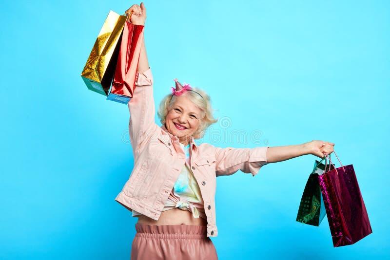 Vieille dame élégante se réjouissant au bargine, nouveaux vêtements photos libres de droits
