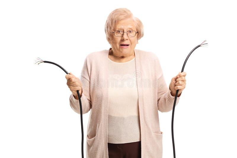 Vieille dame confuse tenant un câble cassé photo stock