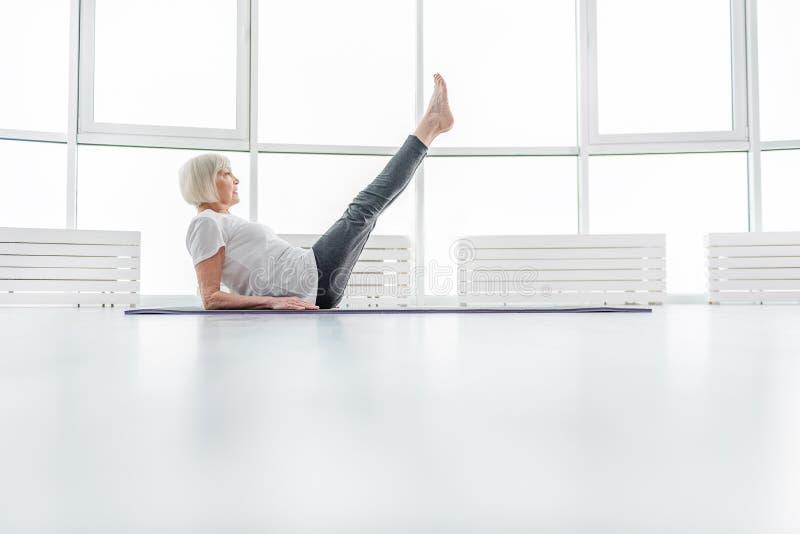 Vieille dame en bonne santé s'exerçant sur le tapis images stock