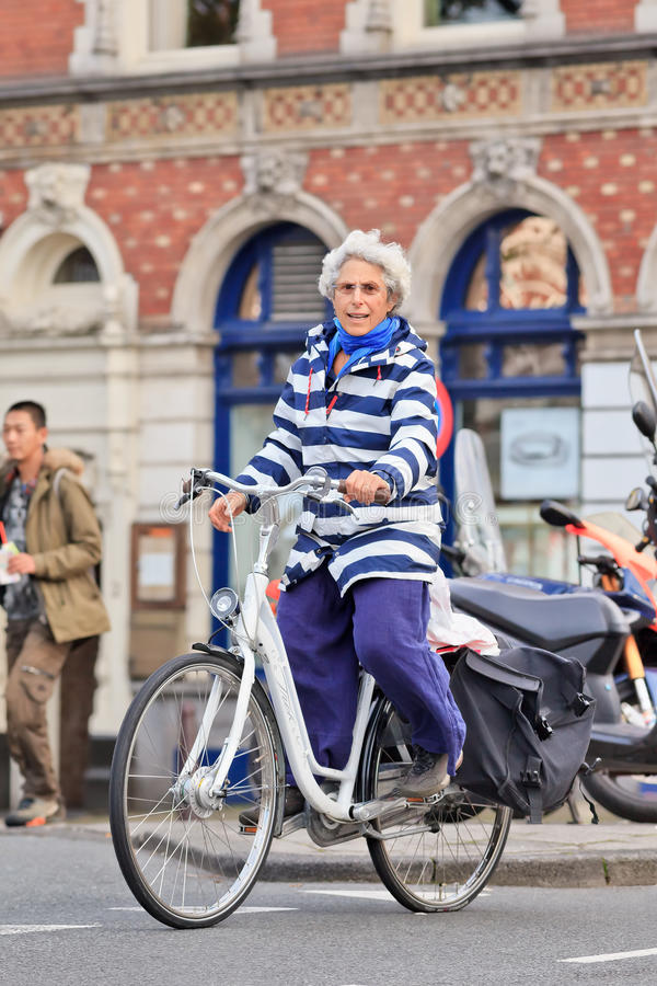 Vieille dame gaie sur une bicyclette blanche, Amsterdam, Pays-Bas photo stock