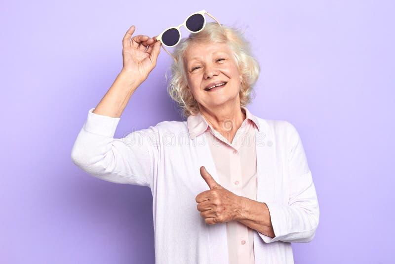 Vieille dame positive de sourire tenant des lunettes de soleil et montrant le pouce  photos libres de droits