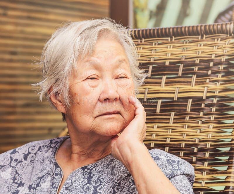 Vieille dame seule assise à la maison, avec la main sur le menton avec un triste images stock