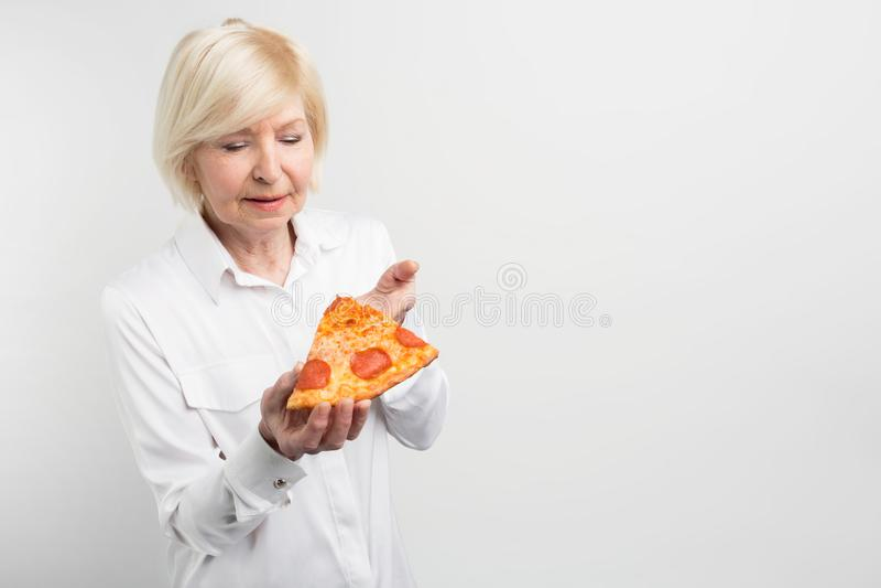 Vieille dame tenant un grand morceau de pizza dans des ses mains Elle essaye de deviner quels ingrédients sont dans lui Également photos stock