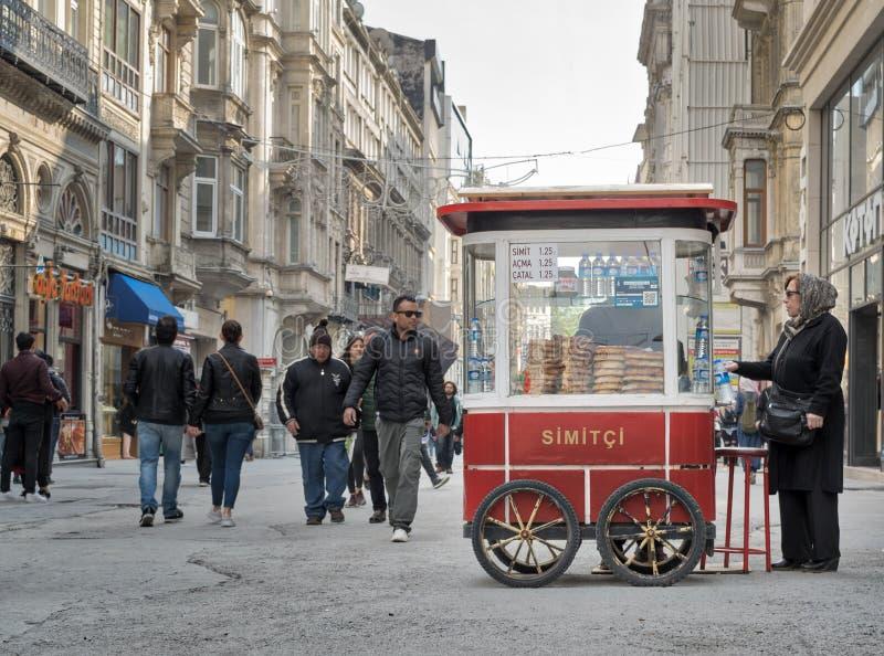 Vieille dame turque achetant le repas de rapide d'un chariot turc de bagel de Simit de turc traditionnel dans la rue d'Istiklal,  photos stock
