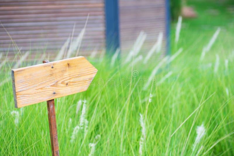 Vieille enseigne en bois de direction de blanc au-dessus d'herbe sur le fond de nature, panneau vide de signe en bois de l'espace images stock