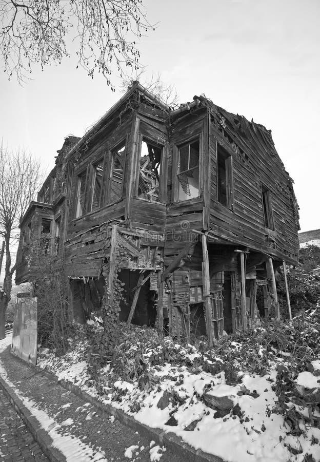 Vieille et ruinée maison dans la neige, photo noire et blanche images stock