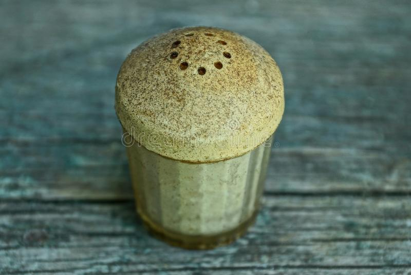 Vieille et sale salière grise en plastique avec du sel sur un conseil en bois photo stock