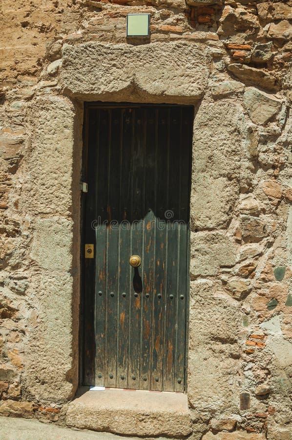 Vieille façade de construction en pierre avec la porte en bois fermée à Caceres photo libre de droits