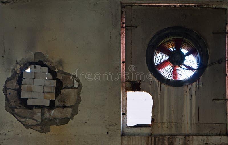 Vieille fan dans le mur de l'usine abandonnée images libres de droits