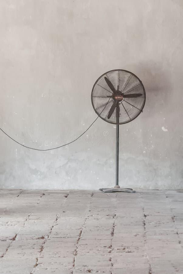Vieille fan noire contre un mur de gris d'épluchage images stock