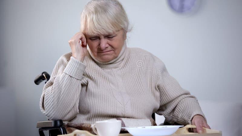 Vieille femelle malheureuse dans le fauteuil roulant refusant de manger le d?jeuner d'h?pital, se sentant isol? photographie stock