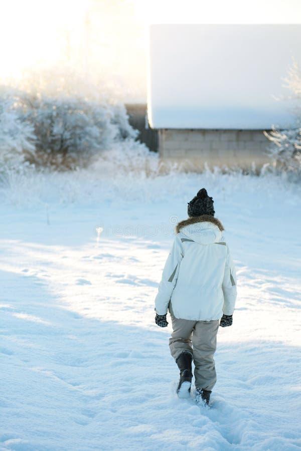 Vieille femme agée dans des vêtements chauds marchant à la maison par la chute de neige importante un matin froid d'hiver au leve photos stock