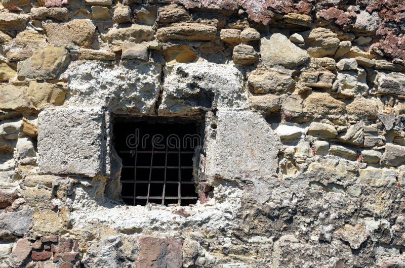 Vieille fenêtre avec des barres dans un mur en pierre photo stock
