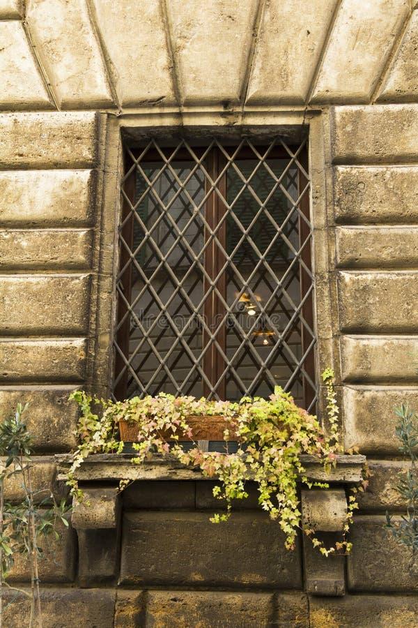 Vieille fenêtre avec des barres dans une ville de Toscane photos stock