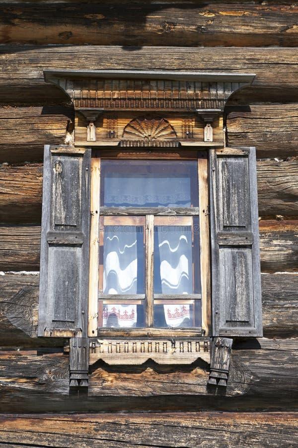Vieille fenêtre avec les volets ouverts en verre avec un ciel bleu sur le fond du mur en bois de la cabane en rondins de campagne photographie stock