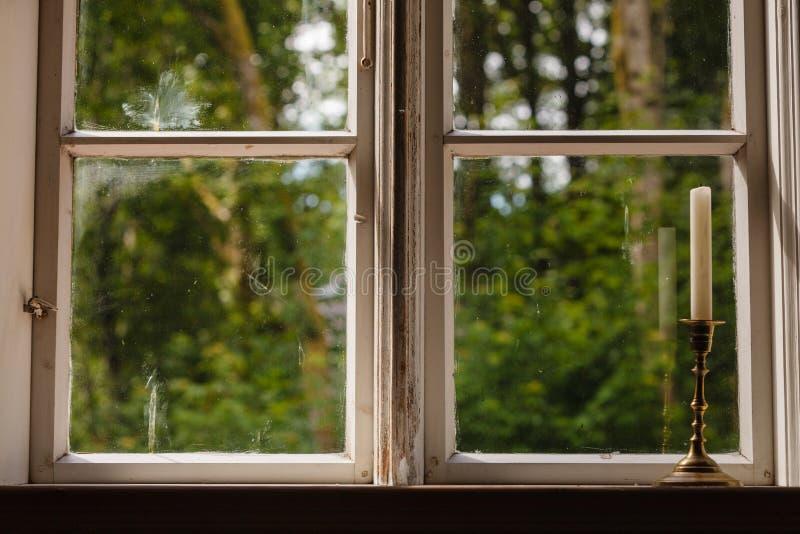 Vieille fenêtre de vintage et bougie verticale dans le chandelier photo stock
