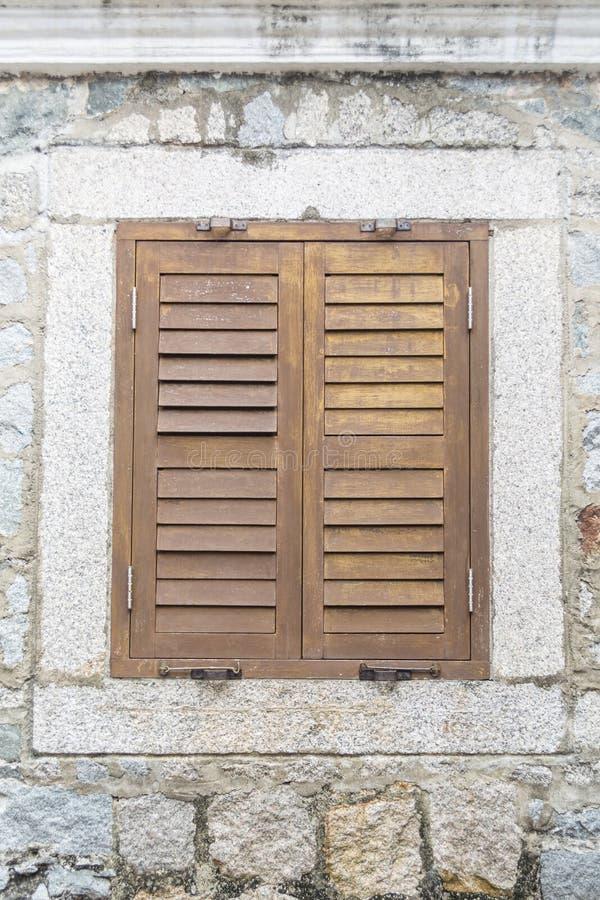 Vieille fenêtre en bois sur le mur en pierre photos libres de droits