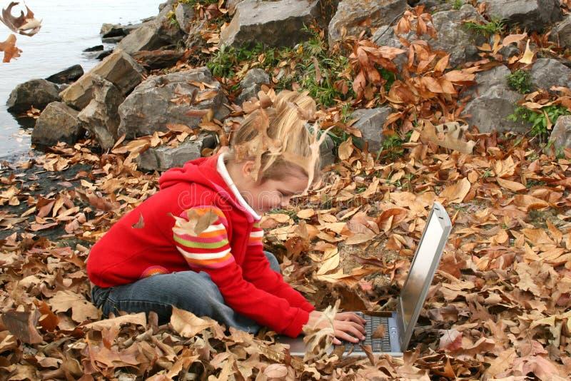 Vieille fille de cinq ans heureuse travaillant à l'extérieur sur l'ordinateur portatif photographie stock libre de droits