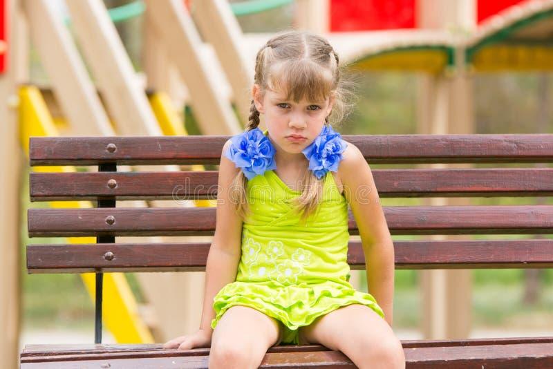 Vieille fille de cinq ans offensée s'asseyant sur un banc au terrain de jeu image libre de droits