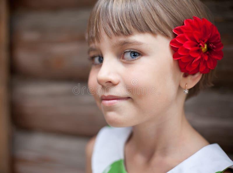 Vieille fille de sept ans avec une fleur rouge dans ses cheveux photos stock