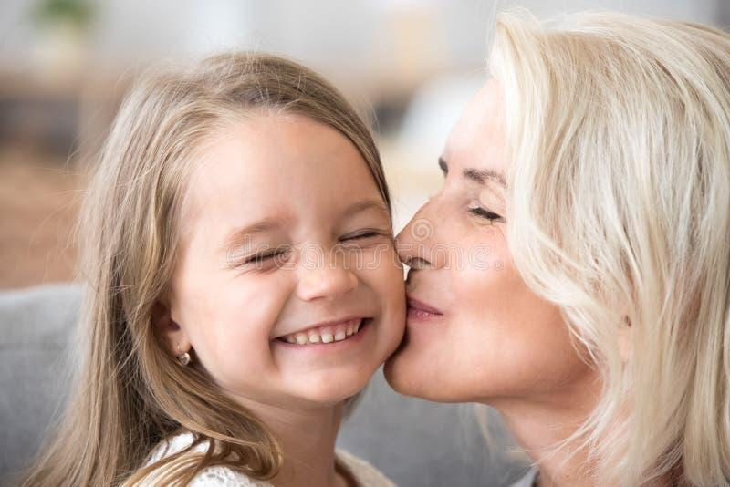 Vieille grand-mère aimante embrassant la petite-fille préscolaire mignonne sur c photographie stock libre de droits
