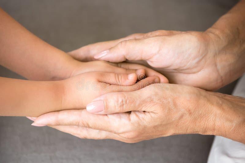 Vieille grand-mère tenant des mains de peu de petite-fille, fin  photos stock