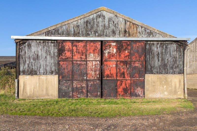 Vieille grange avec des portes en métal, rouillé et rouge images libres de droits