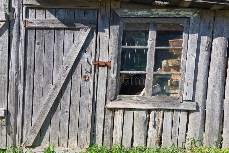 Vieille grange en bois avec une porte fermée et une fenêtre cassée photo libre de droits