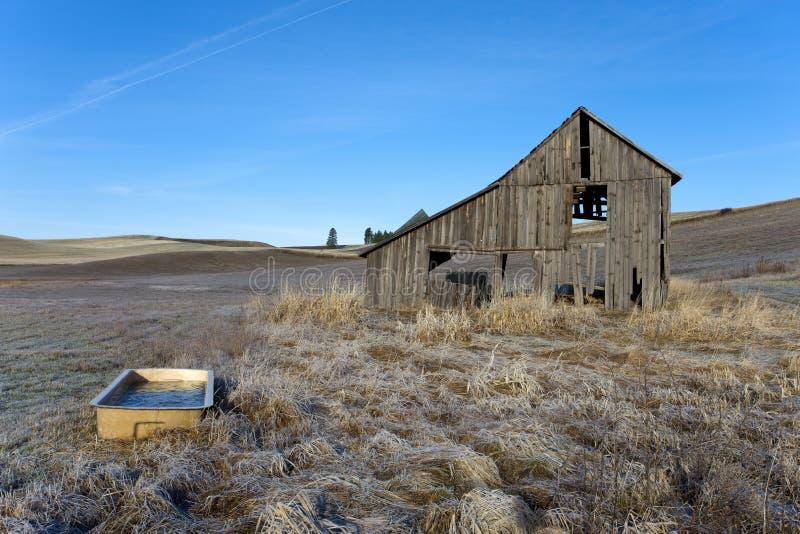 Vieille grange et un baquet. photos stock