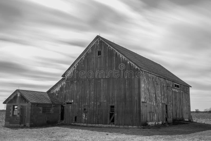 Vieille grange noire et blanche rustique avec le mouvement de nuage photo libre de droits