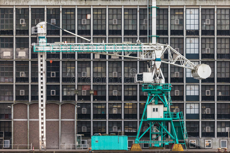 Vieille grue de port devant une usine antique images stock