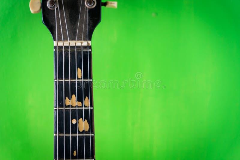 Vieille guitare acoustique sur le mur vert de peinture photo stock