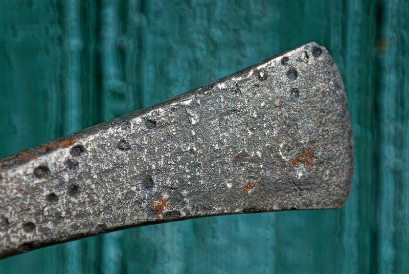 Vieille hache de bataille de fonte grise contre un mur vert photographie stock