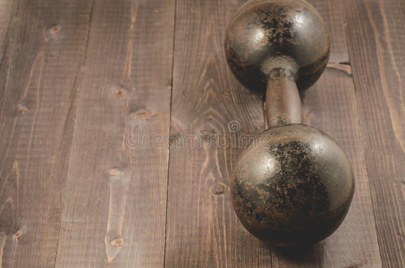 Vieille haltère de fer/vieille haltère de fer sur les WI en bois foncés de fond images libres de droits