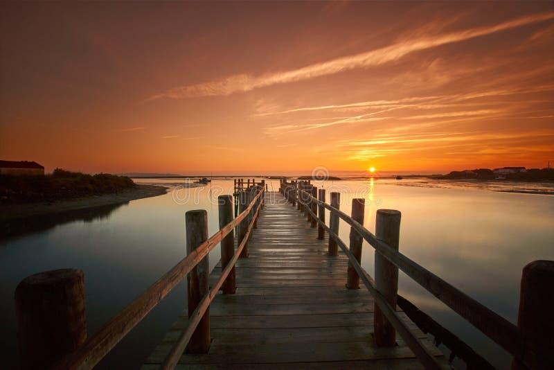 Vieille jetée de mer au lever de soleil sur un lac calme photos libres de droits