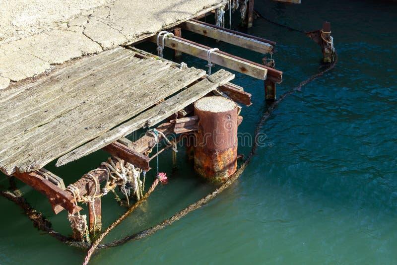 Vieille jetée en bois endommagée au port de mer photos stock