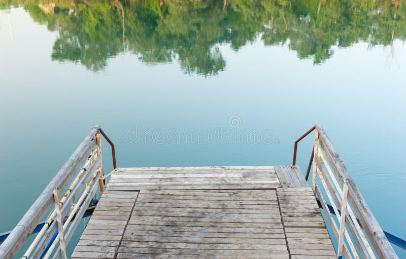 Vieille jetée en bois et rouillée en métal sur un lac photos stock