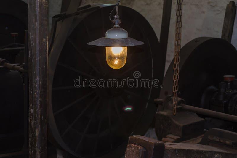 Vieille lampe accrochante dans une usine images libres de droits
