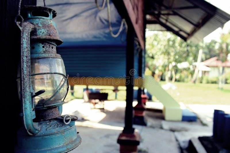 Vieille lampe corrodée d'essence accrochant à la maison de village photographie stock