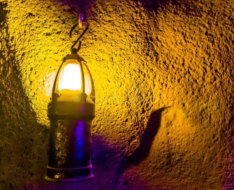 Vieille lanterne allumée fantasmagorique accrochant sur le mur d'une caverne souterraine, fond effrayant de Halloween, objets de  photo stock