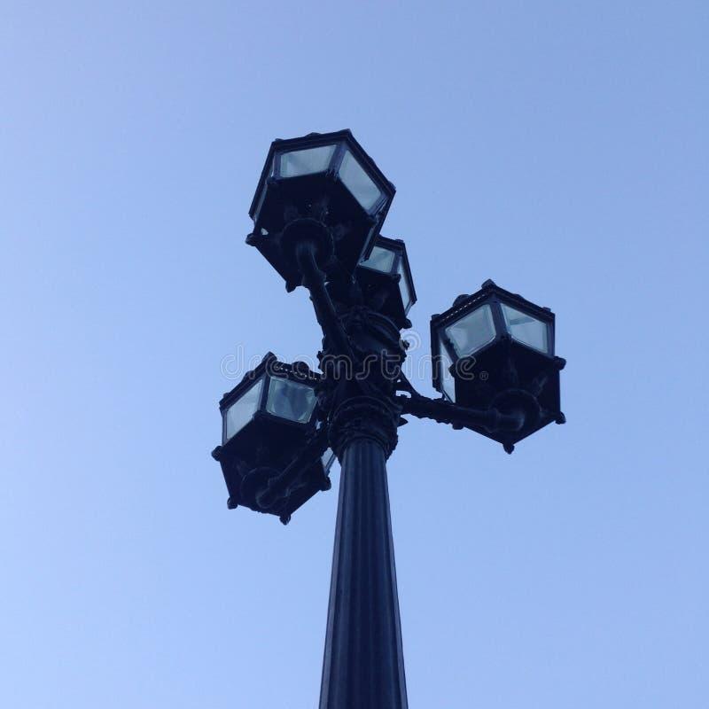 Vieille lanterne de rue de fonte avec quatre lampes derrière le verre contre un ciel bleu lumineux images libres de droits