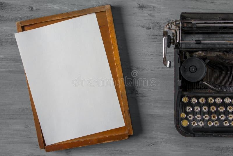 Vieille machine à écrire avec le papier et une boîte photographie stock