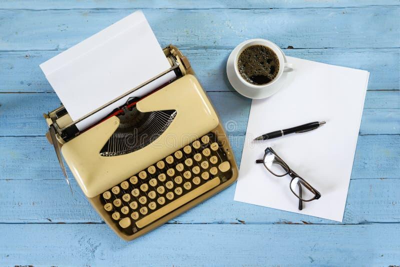 Vieille machine à écrire beige des années 1950 avec le papier, le café et les verres sur une table en bois peinte par bleu, vue c photographie stock