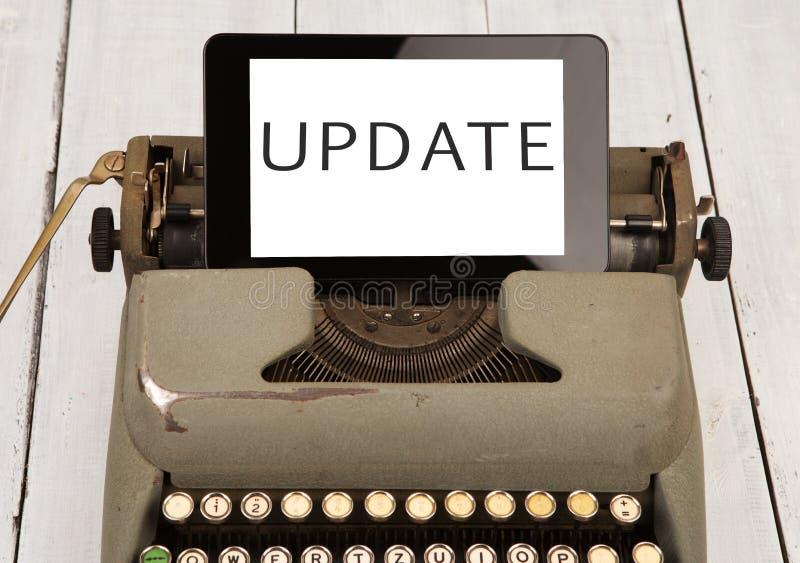 vieille machine à écrire et nouveau PC de comprimé avec le mot et le x22 ; UPDADE& x22 ; sur le fond en bois images stock