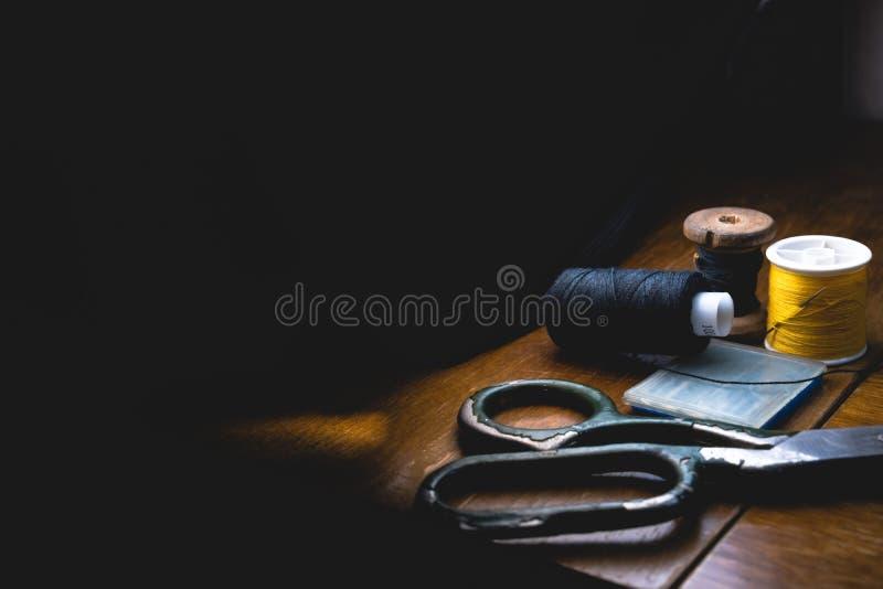 Vieille machine à coudre avec les ciseaux et l'aiguille noirs de fil, sur une vieille table de travail sale Table de travail du ` images stock
