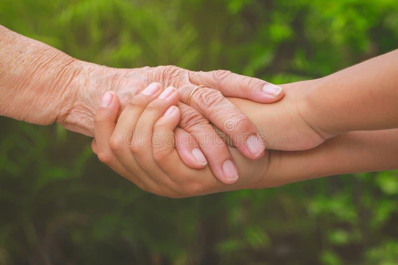 Vieille main femelle tenant de jeunes mains de garçons image libre de droits
